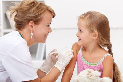 Friendly female nurse administering a vaccination shot to a little girl