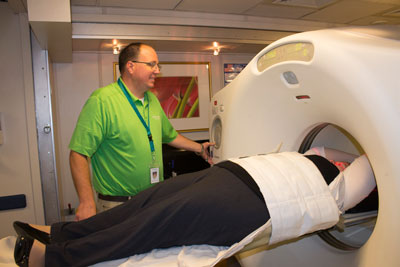 PET/CT technologist raising a patient inside the PET/CT scanner