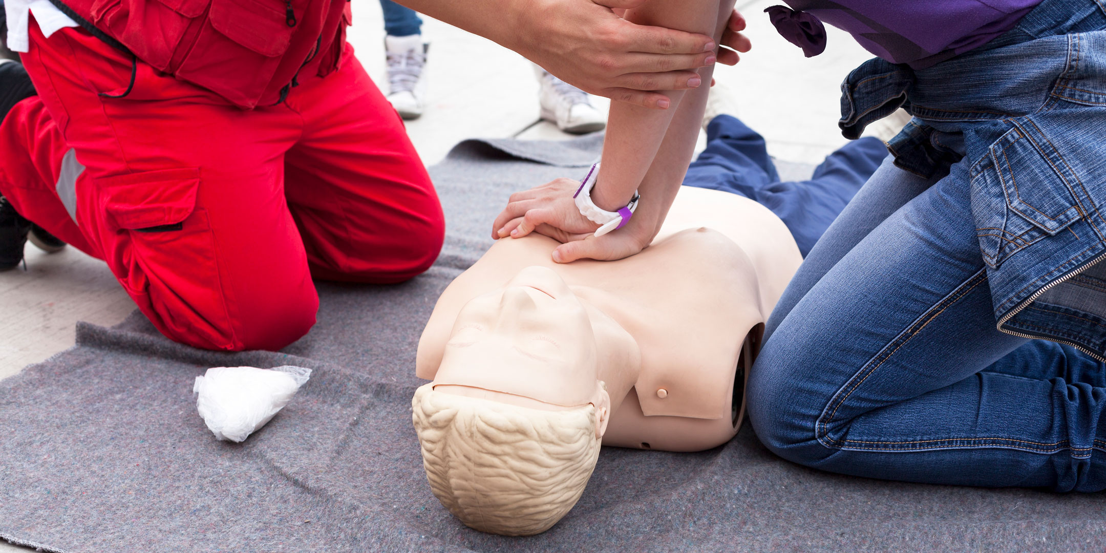 Close-up of CPR instructor helping a student perform CPR on a manikin