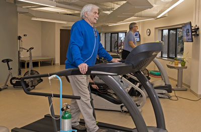 Two cardiopulmonary rehabilitation patients walking on treadmills in the cardiac rehab gym