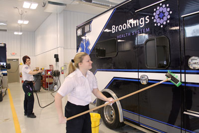 EMT Wendy Long hoses down one of the ambulances housed in the new Ambulance Station and Education Center while EMT Kayley Wika scrubs. Brookings Health invites the public to tour the new station during an open house on Friday, Feb. 22. The new facility creates a headquarters for the ambulance service while also serving the health emergency education needs of the community.