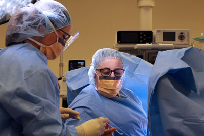 Surgical tech handing Gynecologist Dr. Kirstin Sholes a tool during a surgical procedure