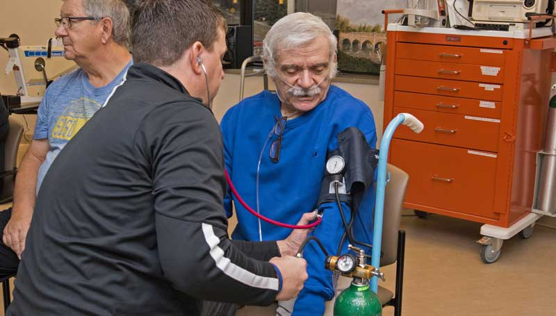Cardiopulmonary rehab patient have his blood pressure taken by a care provider in the cardiopulmonary rehab gym