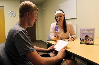 A teenage athlete reads cards from a concussion screening test administered by an occupational therapist