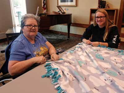 Nursing home resident and SDSU college student pose for the camera while working together on a fleece tie-blanket