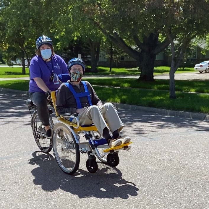 Activities Assistant Jessie Kuechenmeister pedals resident Ron Waltz in one of The Neighborhoods at Brookview's newly purchased tandem wheelchair bikes. The Department of Health recently cleared The Neighborhoods to take residents outside while following COVID-19 guidelines. The timely arrival of the bicycles, which were made possible thanks to a grant from the state, will allow residents to enjoy the freedom of the outdoors this summer.