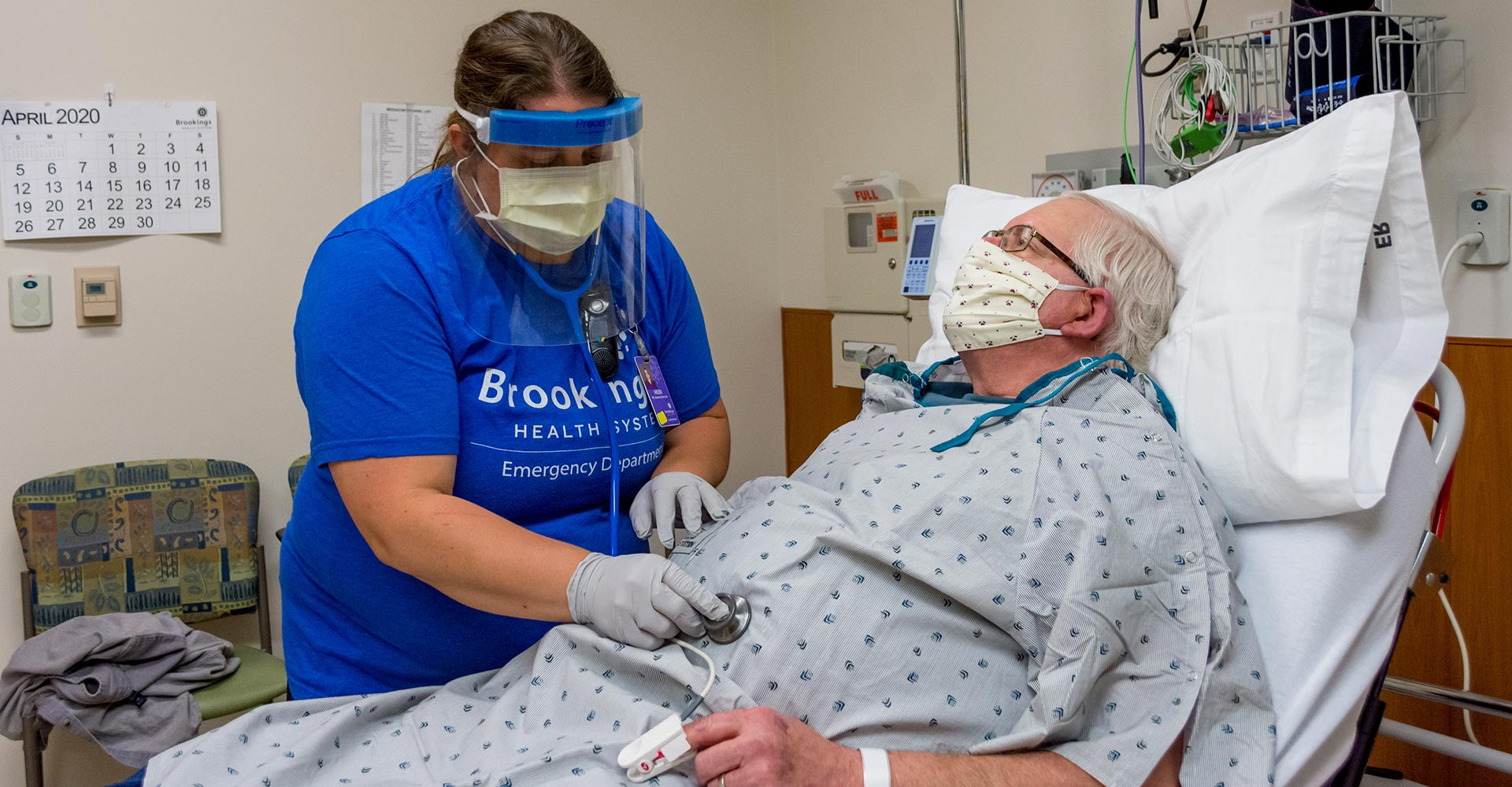 Emergency Room nurse listening to a patient's stomach using a stethoscope while wearing the appropriate personal protective equipment