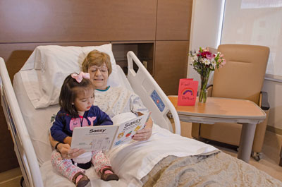 Female patient reading to visiting granddaughter while sitting in bed