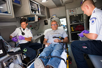 Paramedics treating a patient inside an ambulance