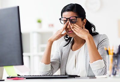 woman sitting in office at computer, itching her eyes