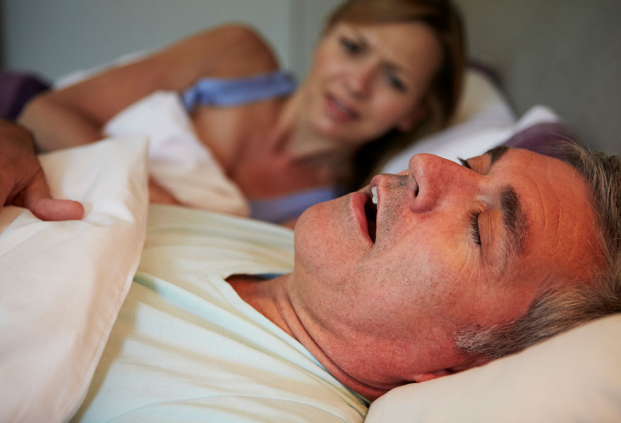 Man snoring in bed with an upset, awake wife in the background