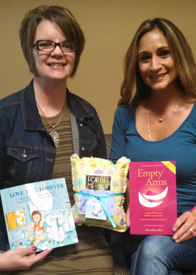Mary Fosness (left) and Amber Hemmestad (right) display the contents of the new Forget-Me-Not comfort care packages now available at Brookings Health System for families of infant loss.