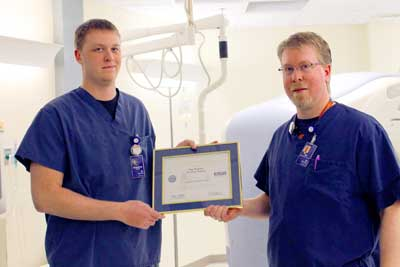 Specialist Ryan Sattler presents his supervisor, Tim Watson, with the Patriotic Employer award.