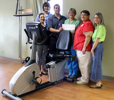 Brookings Healthcare Auxiliary President Sally Damm and Vice President Deb Davis present a check for the new recumbent bike to Brookings Health System's cardiopulmonary rehab staff. Pictured from left to right are Priscilla Hill, Josiah Fitzsimmons, Jesse Walsh, Judy Duffy, Damm, and Davis.