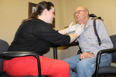 Jim Doyle of DeSmet is examined by Speech-Language Pathologist Becky Cermak.