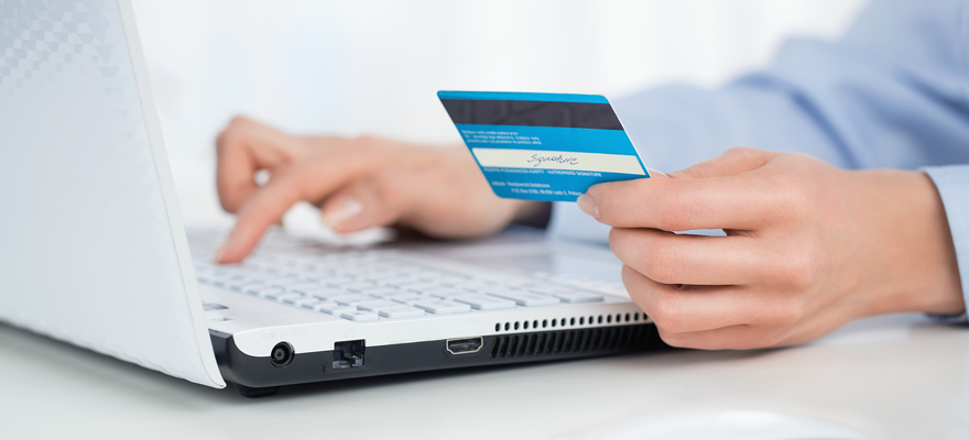 person paying bills online with a credit card