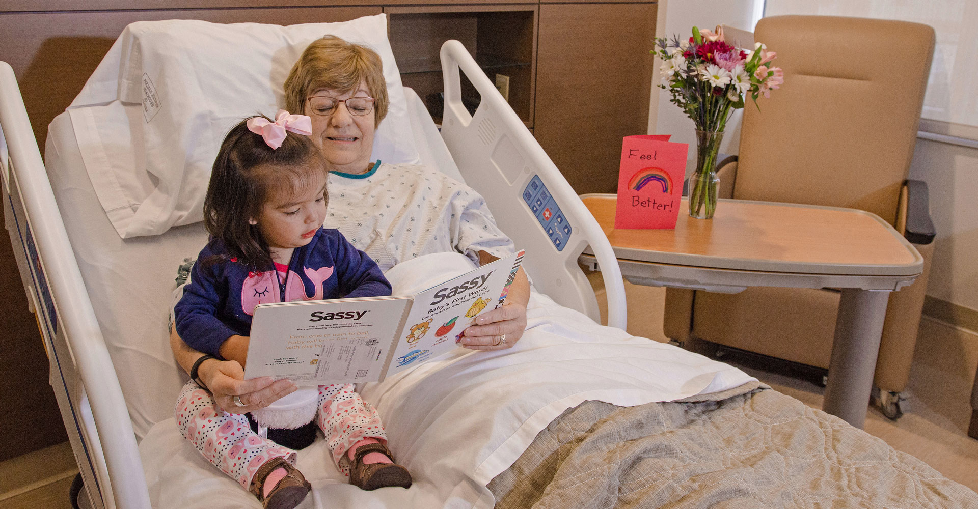 Grandma reading to little granddaughter while she visits grandma in the hospital